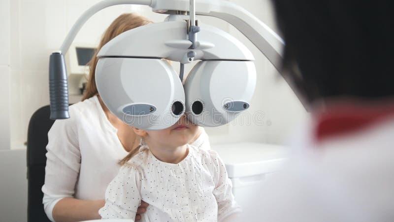 Dziecko okulistyka - optometrist czeków mała dziewczynka oko obraz stock