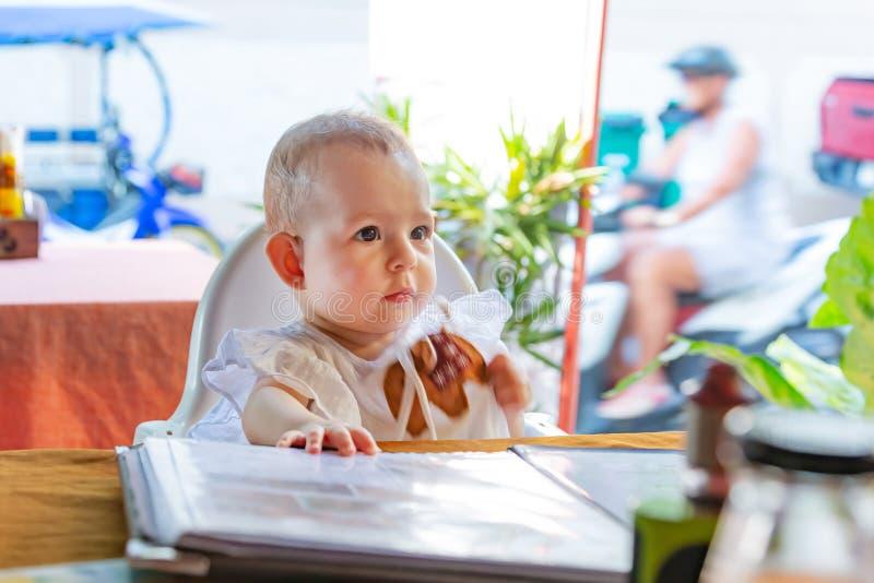 Dziecko ostrożnie patrzeje naprzód Dziecięca dziewczyna siedzi na dziecka wysokim krześle w ulicznej kawiarni obraz royalty free