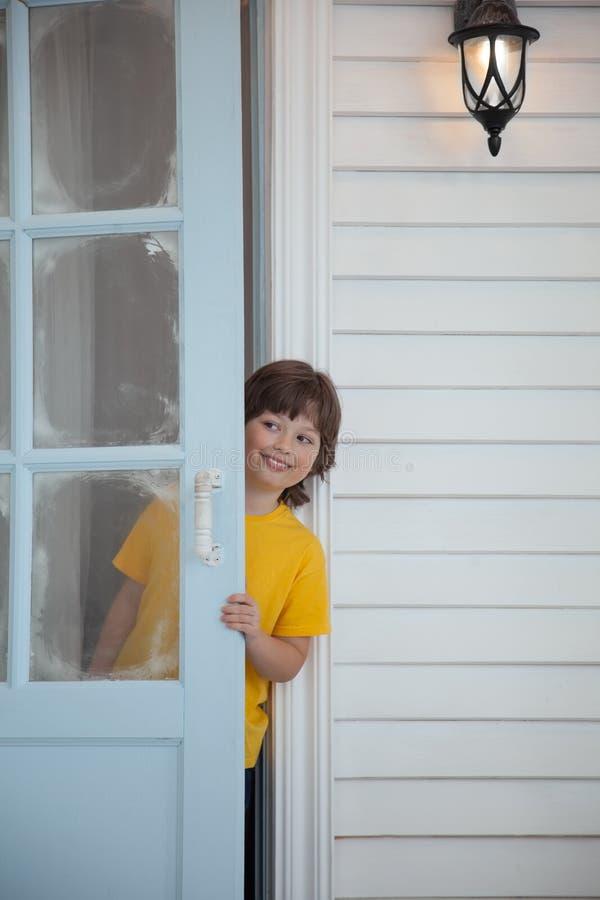 Dziecko otwiera drzwi dom w wiosce obrazy royalty free