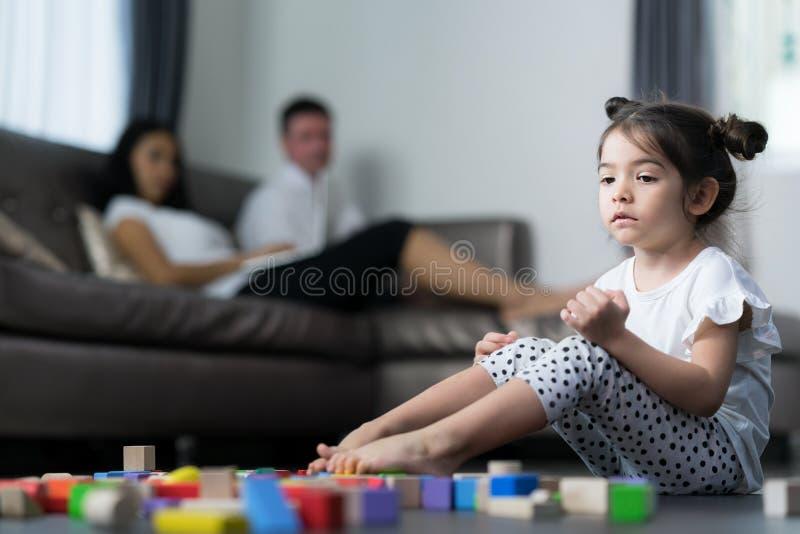 Dziecko płacz i siedzi w żywym pokoju z jej matką i mamą fotografia royalty free