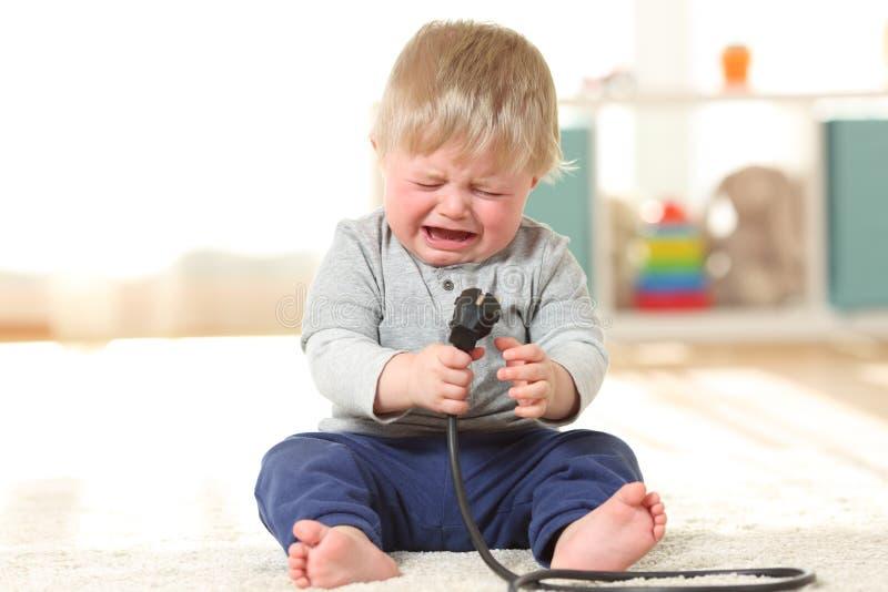 Dziecko płacz trzymający elektryczną prymkę zdjęcia royalty free