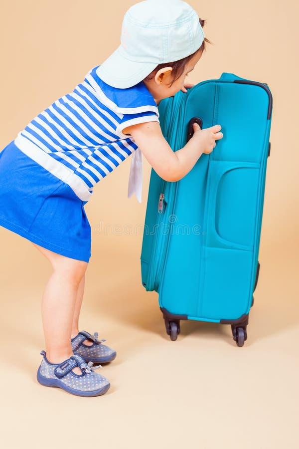 Dziecko pakuje jej rzeczy, odziewa przy bagażem zdjęcia stock