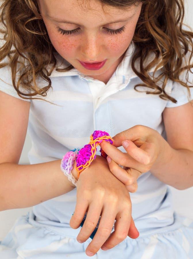 dziecko patrzeje colourful elastyczną bransoletkę fotografia stock
