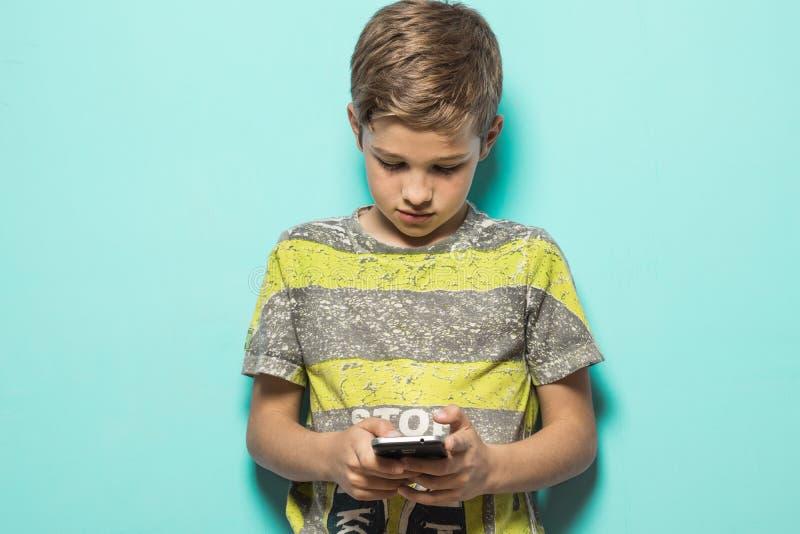 Dziecko patrzeje jego telefon komórkowego obraz royalty free