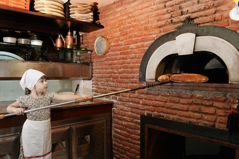 Dziecko piekarz dostaje out chleb od kuchenki fotografia royalty free