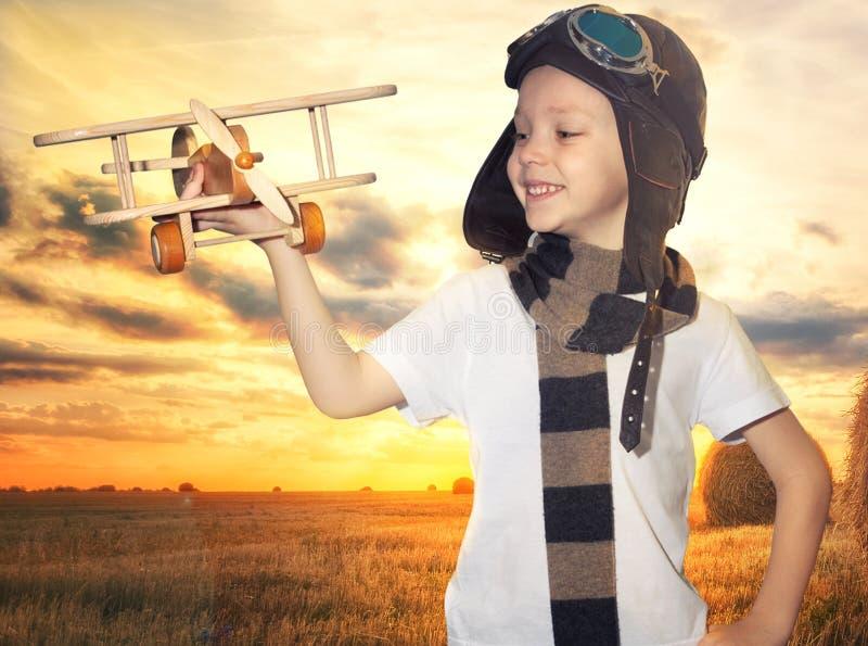 Dziecko pilotowy lotnik z samolotowymi sen podr??owa? w lecie w naturze przy zmierzchem obraz stock