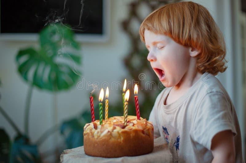 Dziecko podmuchowy za świeczkach na urodzinowym torcie obraz royalty free
