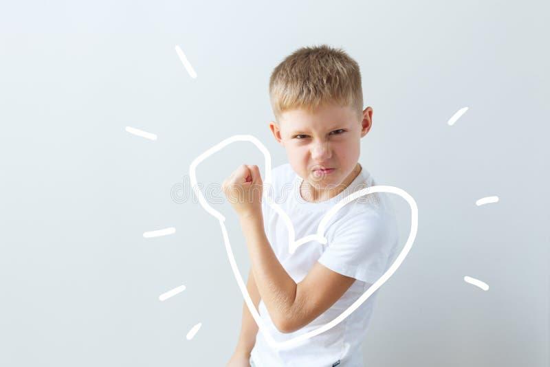 Dziecko pokazuje jego siłę w przegiętej ręce mi??nie fotografia royalty free
