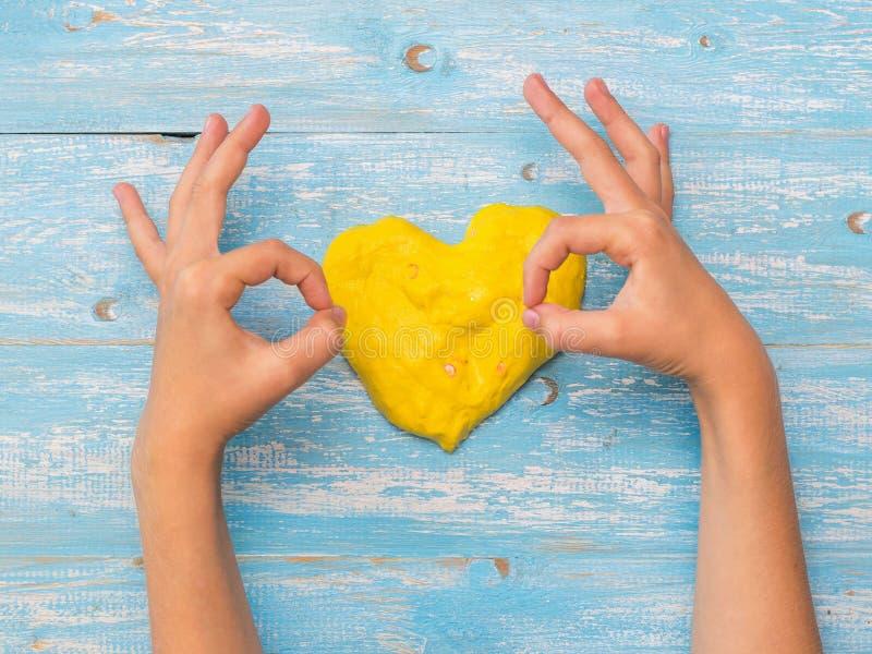 Dziecko pokazuje ręce że wszystko jest dobrze na tle żółci serca obraz stock
