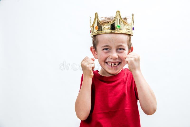 Dziecko postawa z chichotliwymi potomstwami psuł chłopiec z koroną fotografia stock