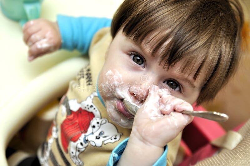 Dziecko próby jeść jogurt niezależnie fotografia stock