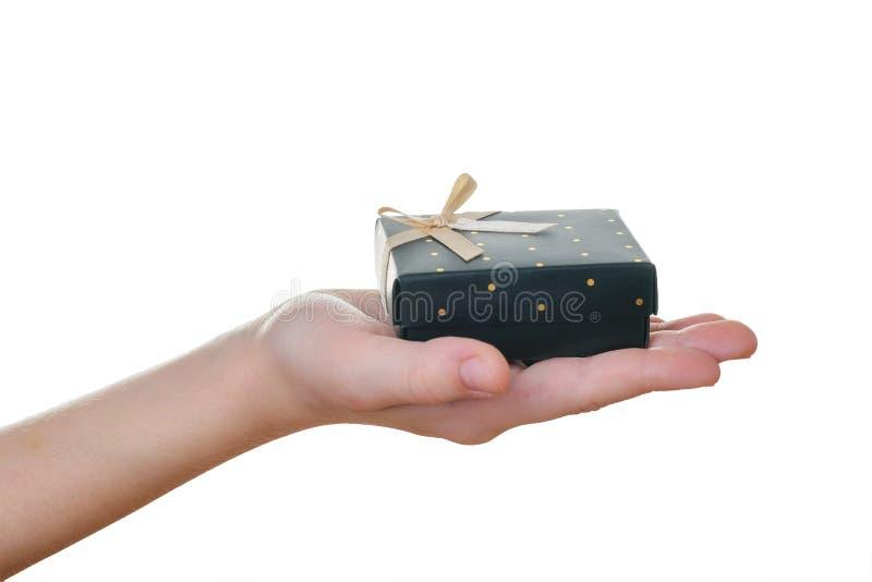 Dziecko prawa ręka z czarnym prezenta pudełkiem odizolowywającym na bielu zdjęcia stock