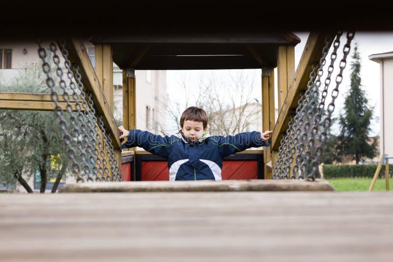 Dziecko przechodzi nad łańcuszkowym mostem w boisku fotografia royalty free