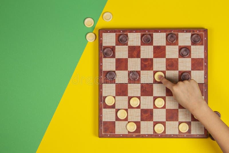 Dziecko ręka bawić się warcabów na checker grą planszowej nad koloru żółtego i zieleni tłem, odgórny widok obraz stock