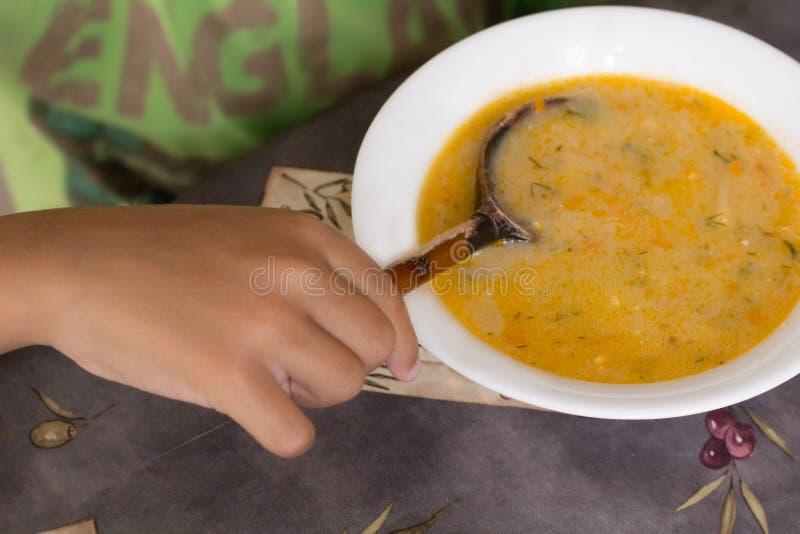 Dziecko ręka trzyma łyżkowego łasowanie ser zupny fotografia stock