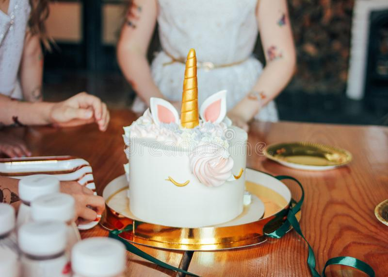 Dziecko ręk małych dziewczynek zasięg dla torta Duża piękna tortowa jednorożec na urodziny mały Princess na świątecznym stole obraz royalty free