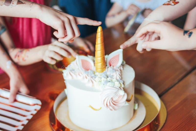 Dziecko ręk małych dziewczynek zasięg dla torta Duża piękna tortowa jednorożec na urodziny mały Princess na świątecznym stole obrazy royalty free