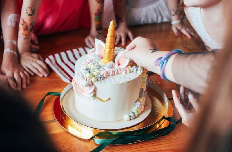 Dziecko ręk małych dziewczynek zasięg dla torta Duża piękna tortowa jednorożec na urodziny mały Princess na świątecznym stole obraz stock
