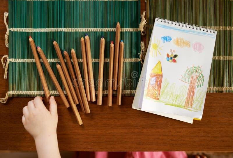 Dziecko ręka bierze ołówek na stole remis obrazy stock