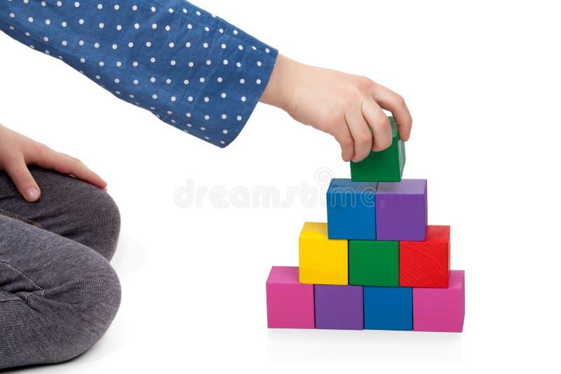 Dziecko ręka buduje cegły wierza odizolowywający na białym tle obrazy royalty free