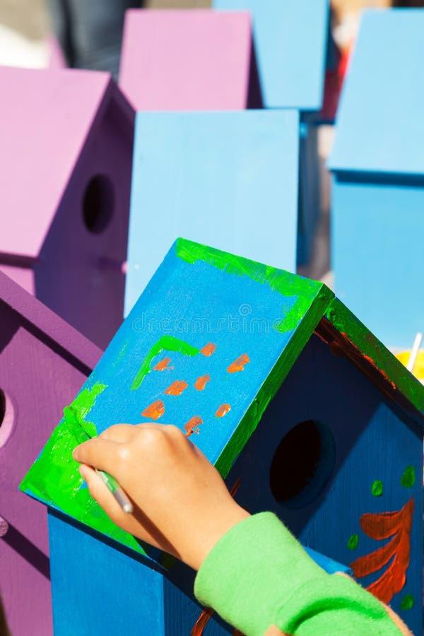 Dziecko ręka maluje birdhouse jaskrawych kolory błękit i purpury zdjęcie royalty free