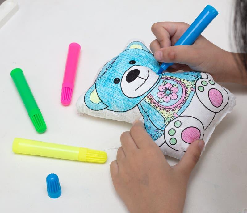 Dziecko ręki barwi zabawka niedźwiedzia z akwareli piórami zdjęcia stock