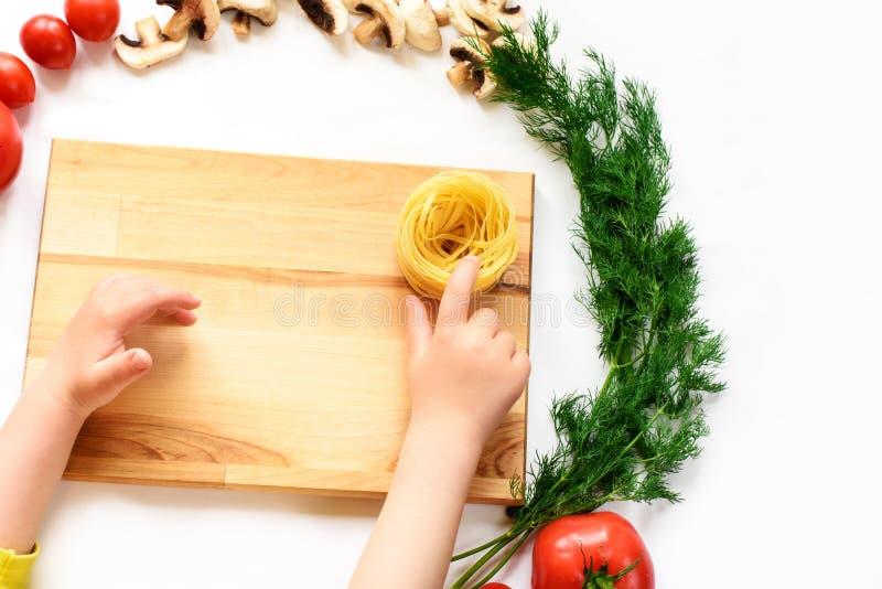 Dziecko ręki dotyka makaron gniazdują na drewnianym biurku, warzywa fotografia royalty free