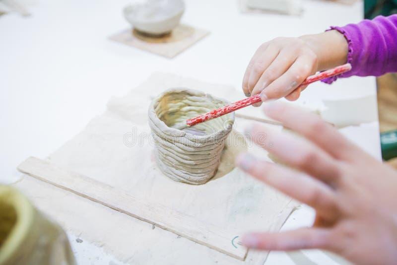 Dziecko ręki maluje z szczotkarskimi zawdzięczający sobie glinianymi rzeczami fotografia royalty free