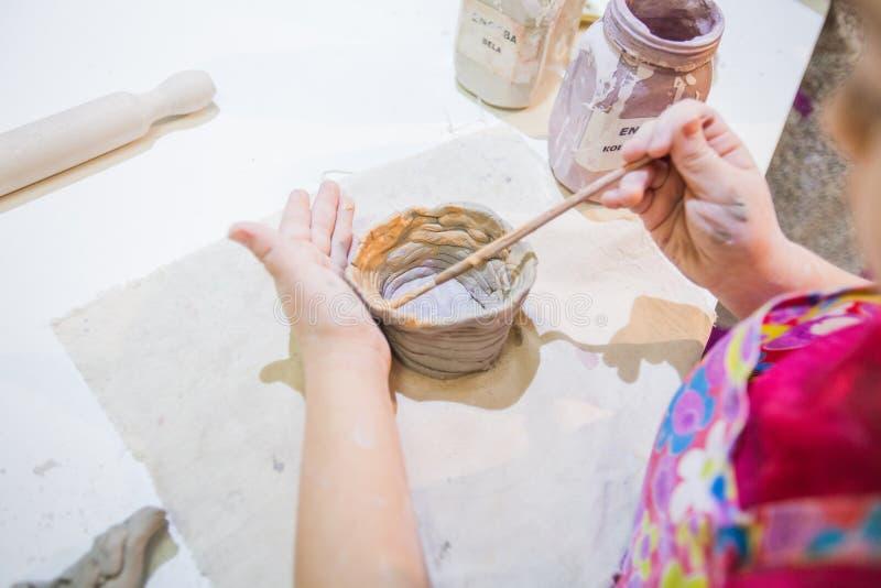 Dziecko ręki maluje z szczotkarskimi zawdzięczający sobie glinianymi rzeczami zdjęcie stock