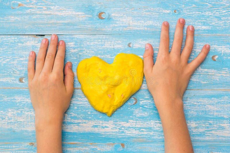 Dziecko ręki na stole z kolorem żółtym śluzowacieją w postaci serca obraz stock