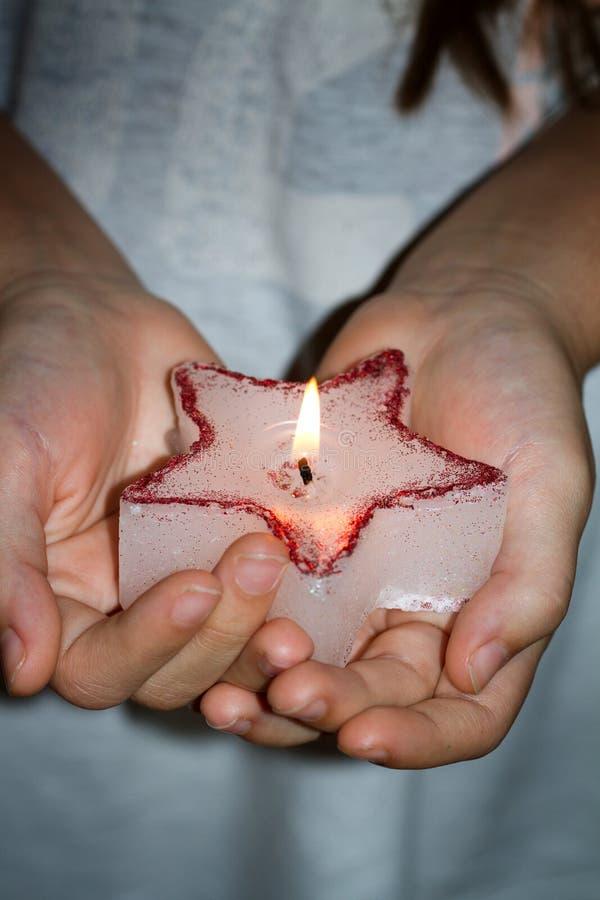 Dziecko ręki trzyma świeczek boże narodzenia grają główna rolę w noc znaku nadziei pojęcie zdjęcia royalty free
