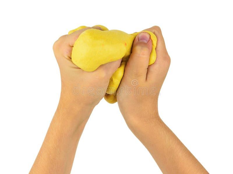 Dziecko ręki ugniatają koloru żółtego szlamowy odosobnionego na białym tle obrazy royalty free