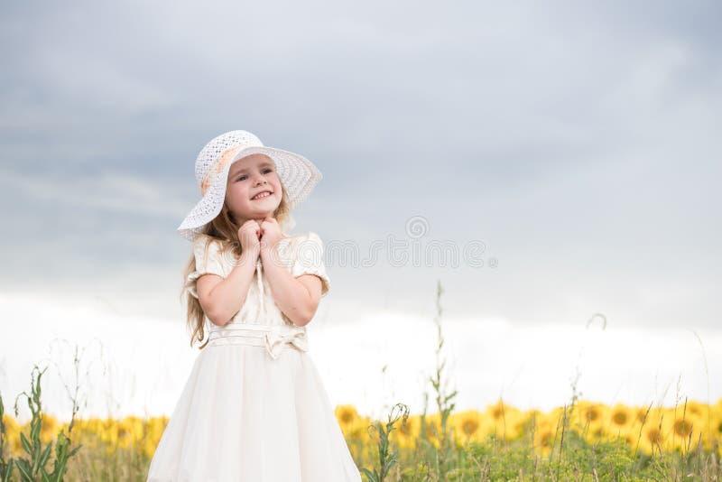Dziecko raduje się ono uśmiechać się piękna dziewczyna w białej sukni i białym kapeluszu zdjęcie stock