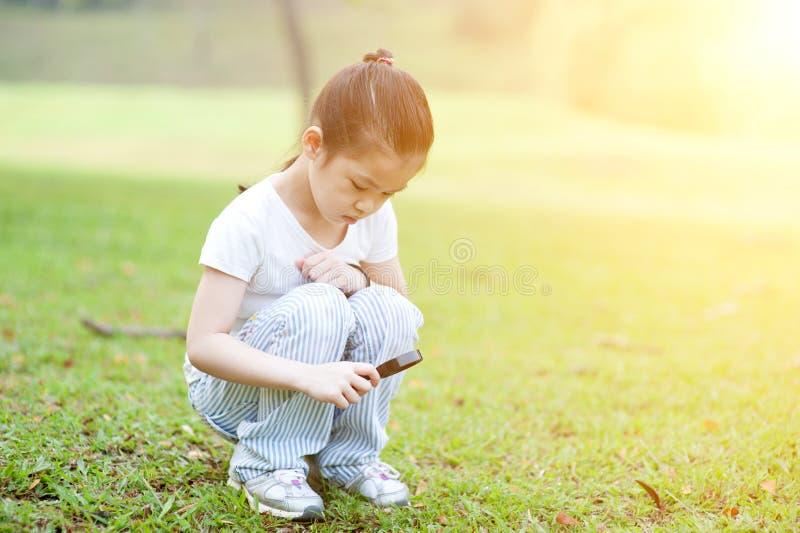 Dziecko rekonesansowa natura z magnifier szkłem przy outdoors obrazy royalty free