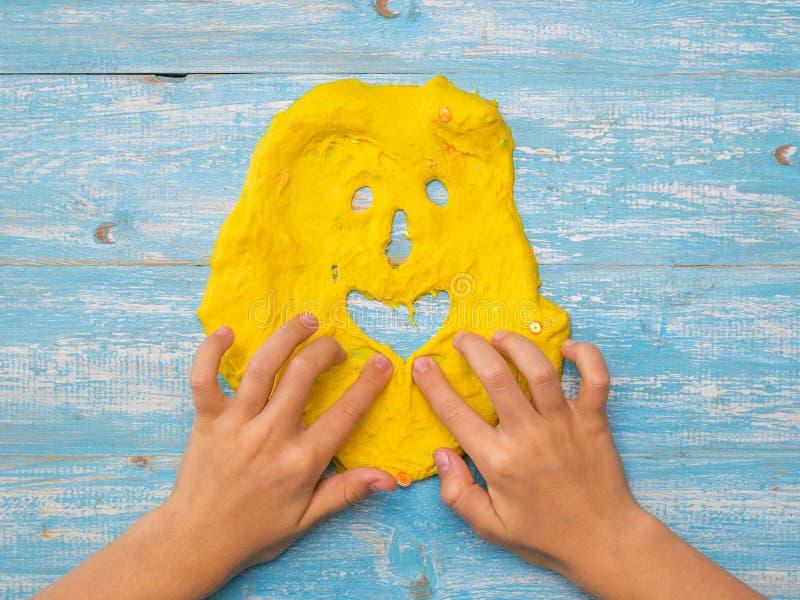 Dziecko robi śmiesznej twarzy szlamowa kolor żółty na błękitnym stole fotografia royalty free