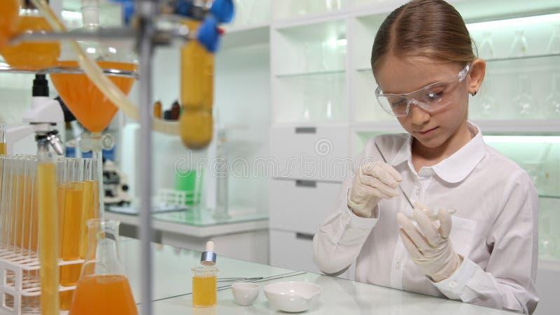 Dziecko Robi Chemicznemu eksperymentowi w Szkolnym Lab, Studencka dziewczyna w nauki klasie obraz royalty free