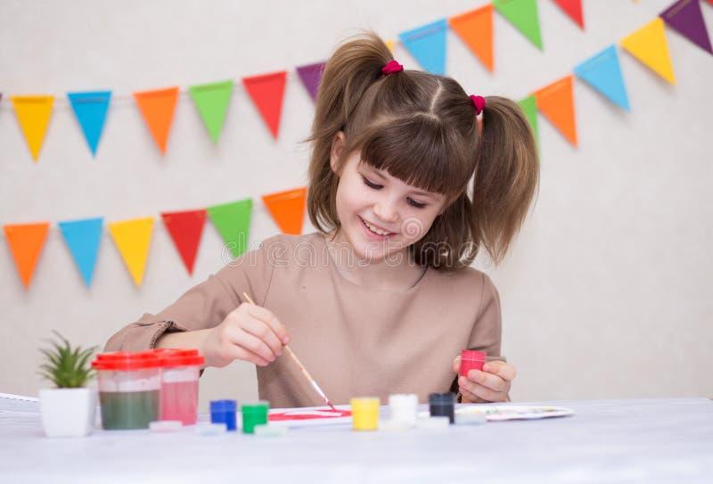 Dziecko robi domowej roboty kartka z pozdrowieniami Mała dziewczynka maluje serce na domowej roboty kartce z pozdrowieniami jako  obrazy royalty free
