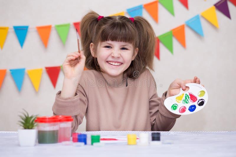 Dziecko robi domowej roboty kartka z pozdrowieniami Mała dziewczynka maluje serce na domowej roboty kartce z pozdrowieniami jako  zdjęcia royalty free