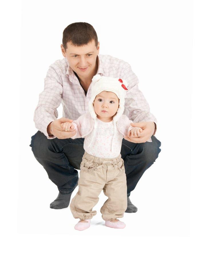 Dziecko robi pierwszym krokom z ojciec pomocą zdjęcia stock