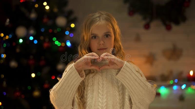 Dziecko robi sercu z rękami patrzeje kamera, miłość i dobroczynność, przy bożymi narodzeniami zdjęcie royalty free