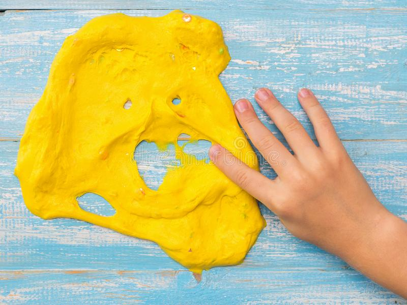 Dziecko rozciąga jego prawa ręka twarz szlamową na błękitnym stole kolor żółty obraz stock