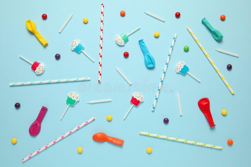 Dziecko rozochocony wystrój dla przyjęcia, błękitny tło Słodcy cukierki, jaskrawe piłki, świąteczne świeczki i słoma, zdjęcie stock