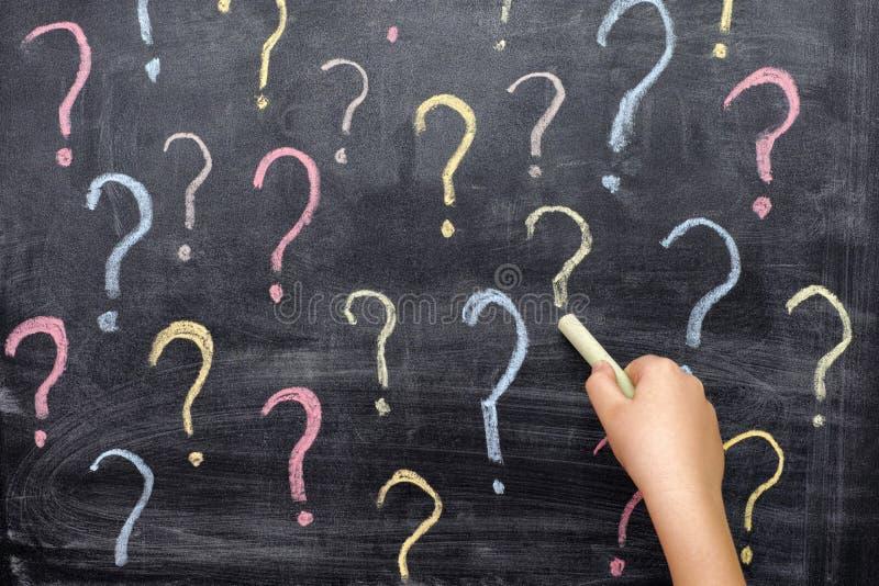 Dziecko rysuje kolorowych znaki zapytania na blackboard zdjęcia royalty free