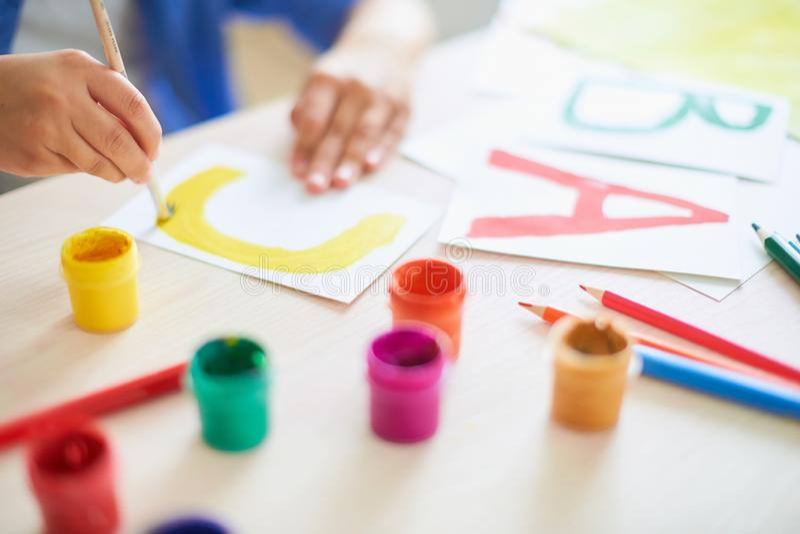 Dziecko rysuje z akwareli szczotkarskimi farbami dalej tapetuje list C obraz stock