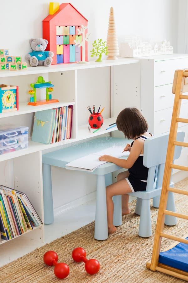 Dziecko siedzi przy stołem w dziecka ` s pokoju rysuje z ołówkami fotografia stock