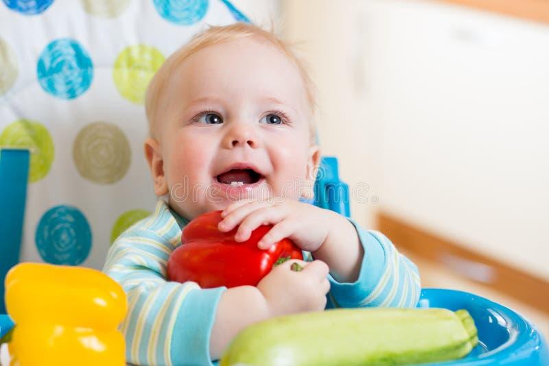 Dziecko siedzi w krześle na kuchni z warzywami fotografia stock