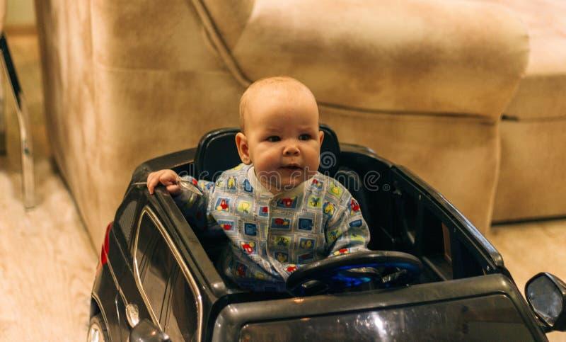 Dziecko siedzi w zabawkarskim samochodzie, bawić się, próbuje iść obraz royalty free