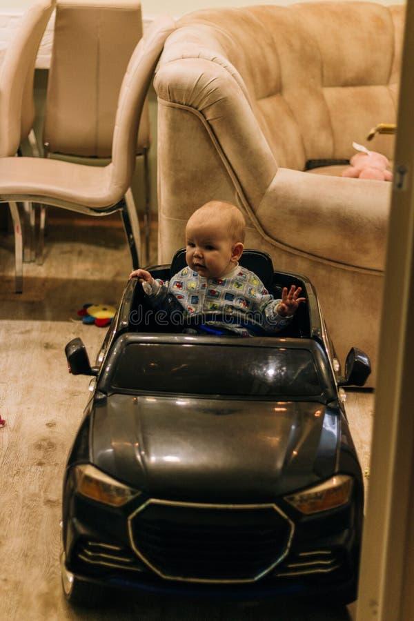 Dziecko siedzi w zabawkarskim samochodzie, bawi? si?, pr?buje i?? obrazy stock