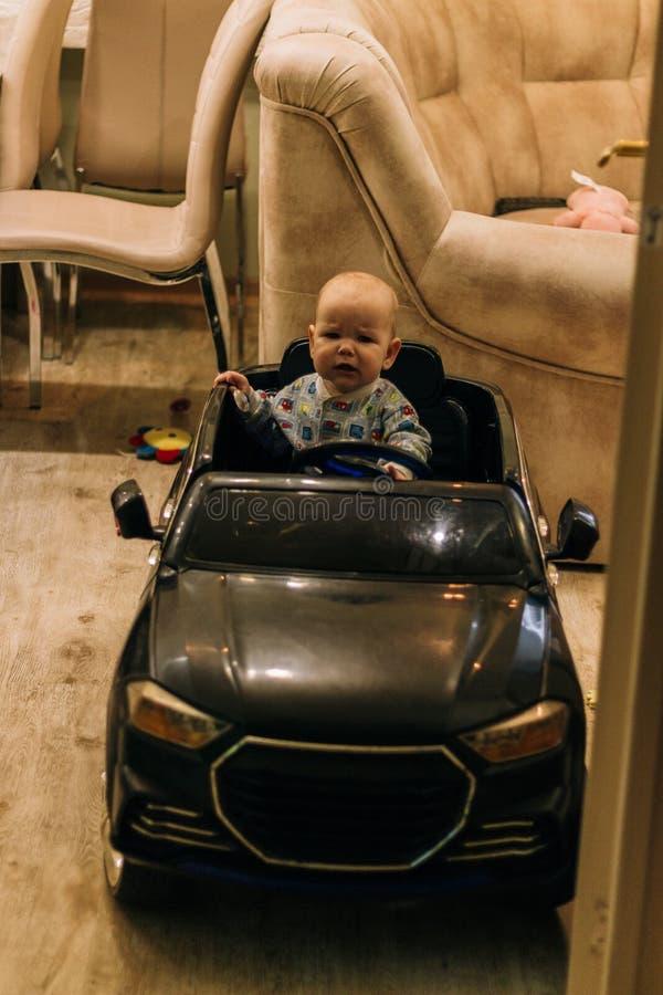 Dziecko siedzi w zabawkarskim samochodzie, bawi? si?, pr?buje i?? obraz stock