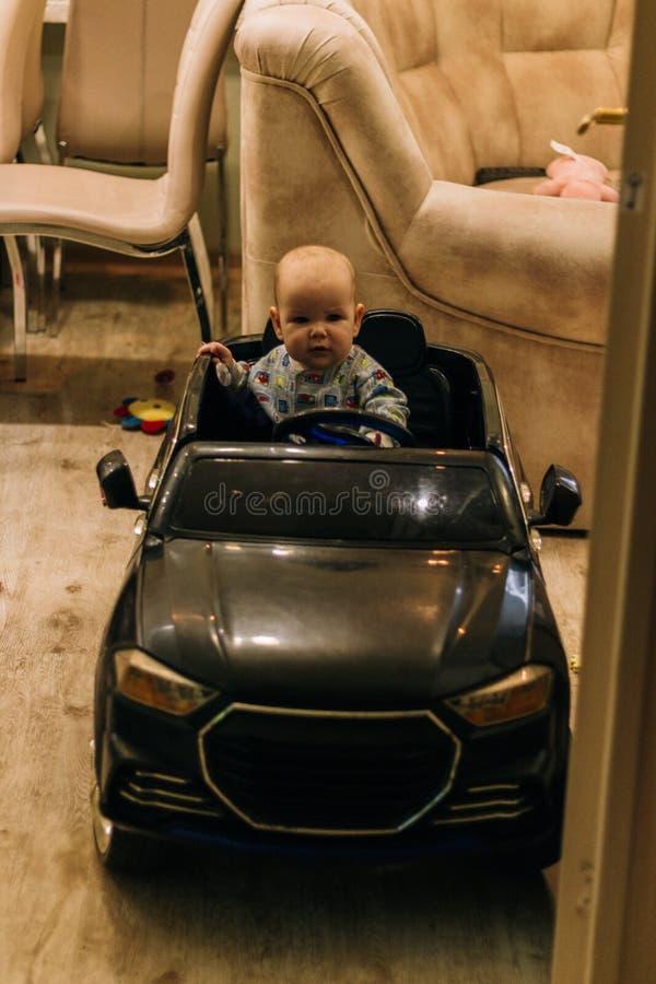Dziecko siedzi w zabawkarskim samochodzie, bawi? si?, pr?buje i?? zdjęcie stock